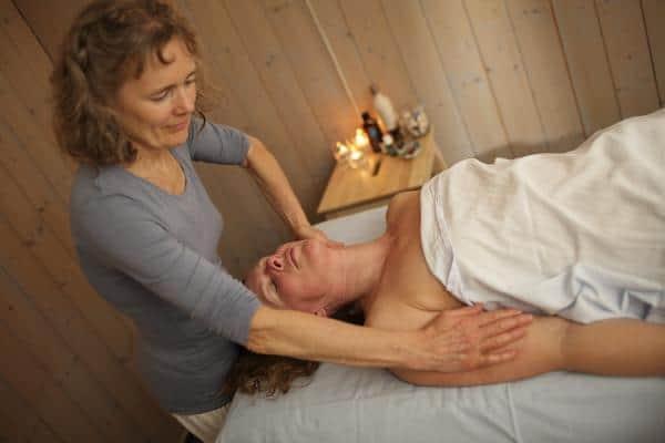 Person som ligger på benk og får massasje