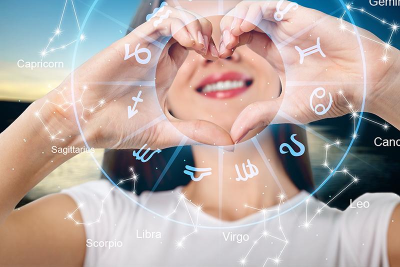 Kvinne smiler og lager hjertetegn med hendene, stjernetegn symboler i sirkel rundt hendene