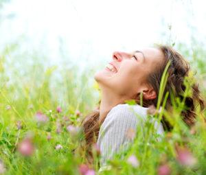 Vakker ung kvinne utendørs i blomstereng, nyter naturen