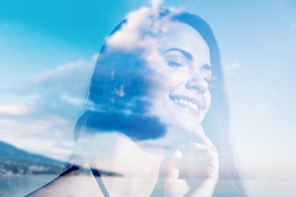 Kvinne som smiler, sammenblandet med skyer og himmel