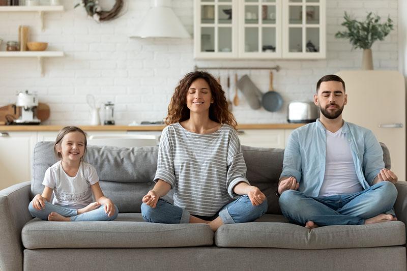 Familie sitter i sofa og mediterer