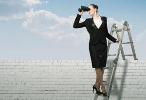 Dame står på stige og ser i kikkert.