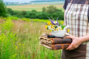 Kvinn i eng, holder bok og urter
