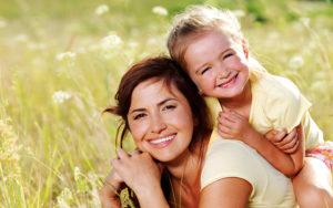 Kvinne og barn i eng, smiler