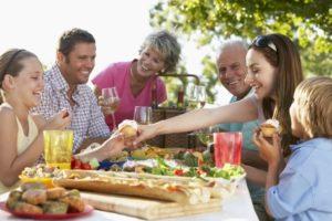 Familie sitter ved bord og spiser ute.